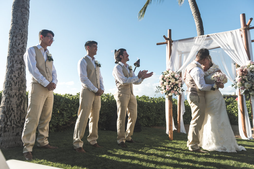 groomsmen look on as bride and groom kiss in maui