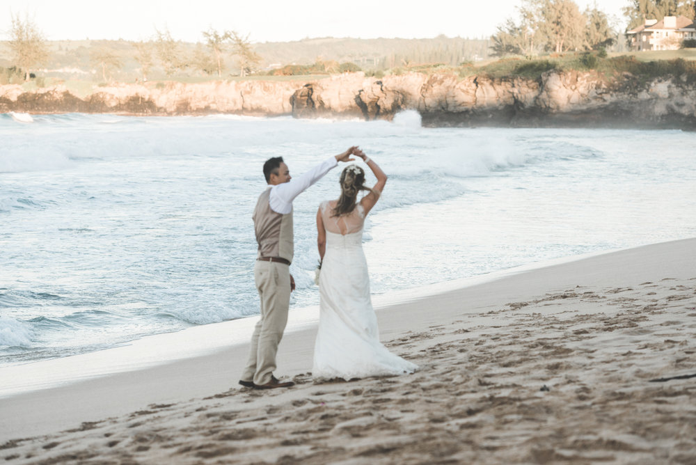 groom twirls bride around on maui beach