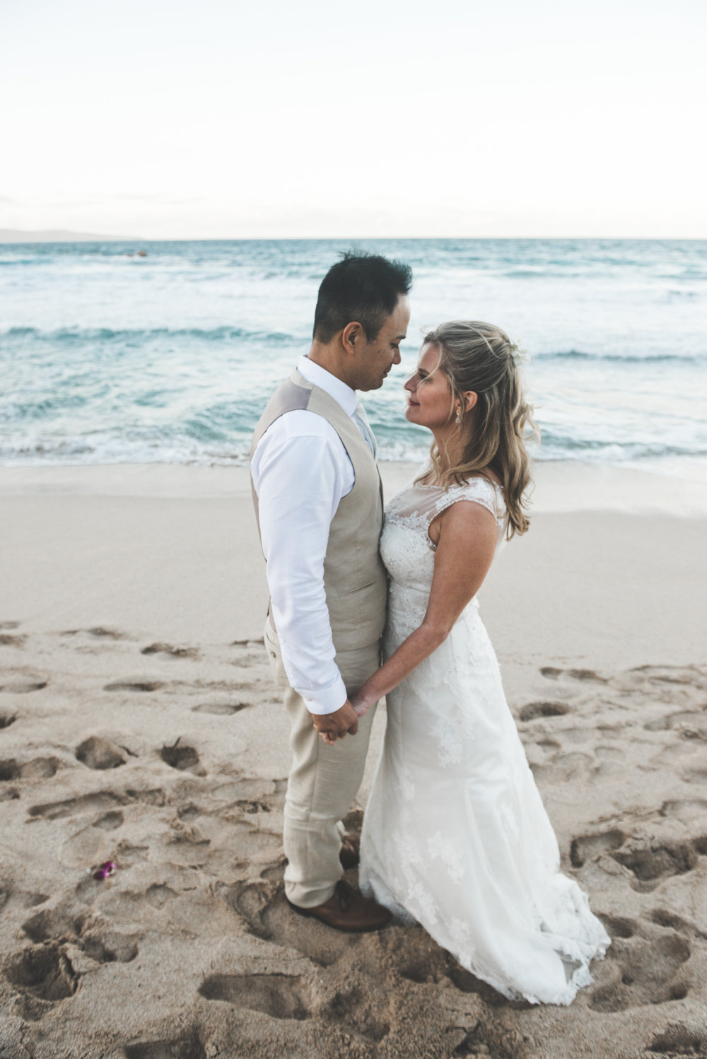 bride and groom gaze at each other on sandy maui beach