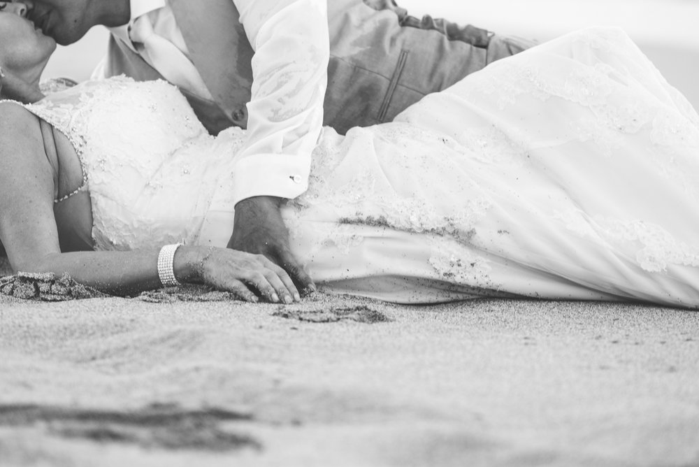 bride and groom on wet sand trash the dress maui