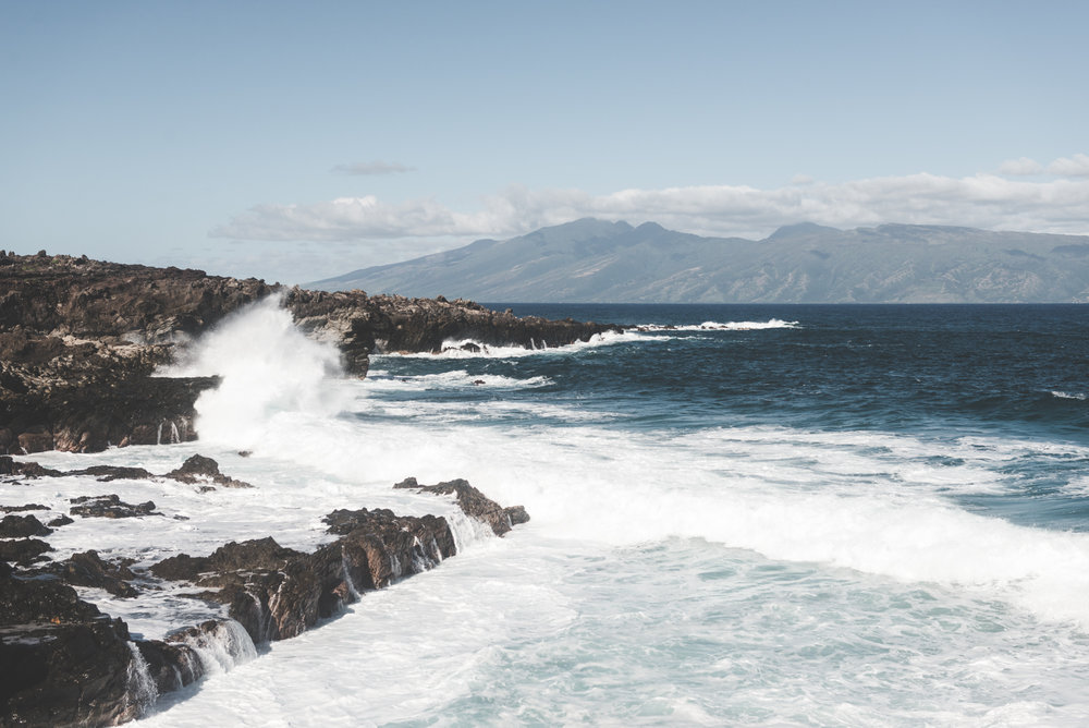 waves crash on lava rock on west maui beach