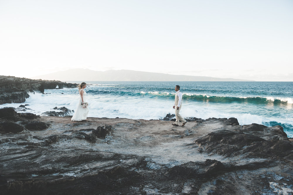 bride and groom on lava rocks with crashing waves