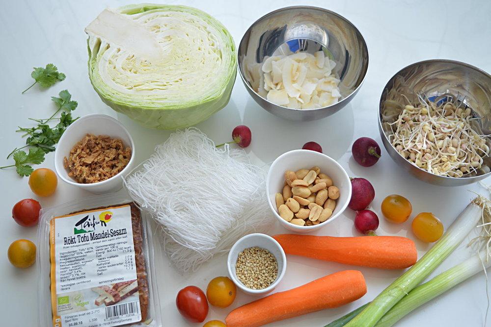 Ingredienser till glasnudelssallad: Glasnudlar, vitkål, morötter, mungbönsgroddar, körsbärstomater, salladslök, rökt tofu, rostad kokos, sesamfrön, jordnötter och lök.