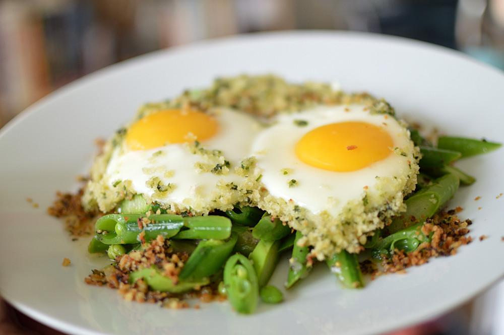 Stekt ägg med vitlökskrisp på med sparris och salladsärtor.