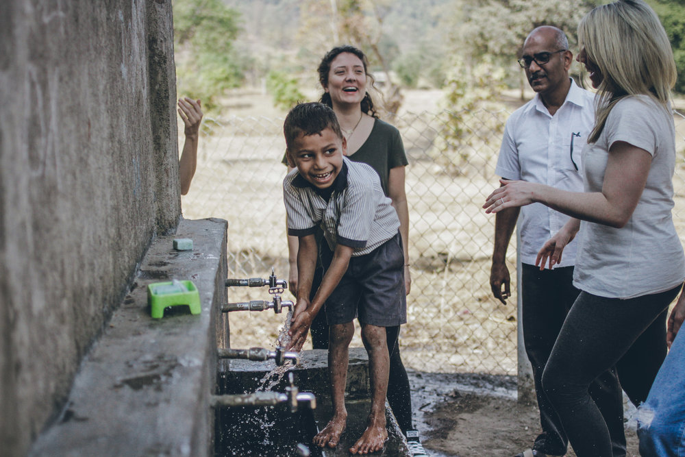 Handwashing in action at Ashte Nursery School, with Michelle, Kenneth and one of our board members Libby, during our February 2017 visit. Photo credit: Karan Khosla.