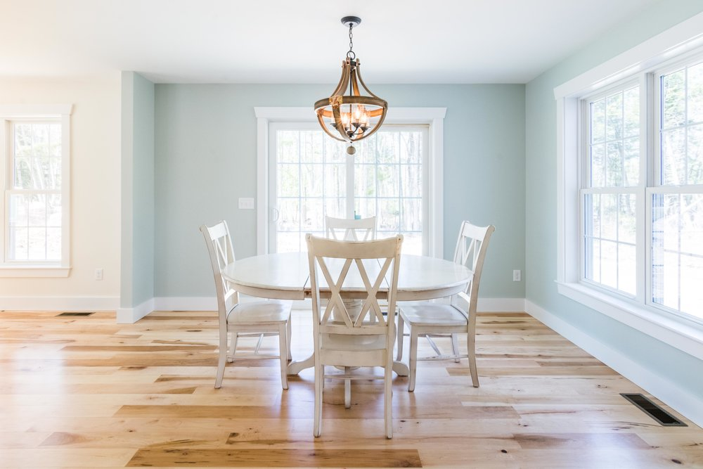 The dining area and living room flow into one another, forming a U shape around the staircase, delineated by a subtle change in wall color. The dining is painted with Sea Salt from Sherwin Williams, and the living is Creamy, also from Sherwin Williams.