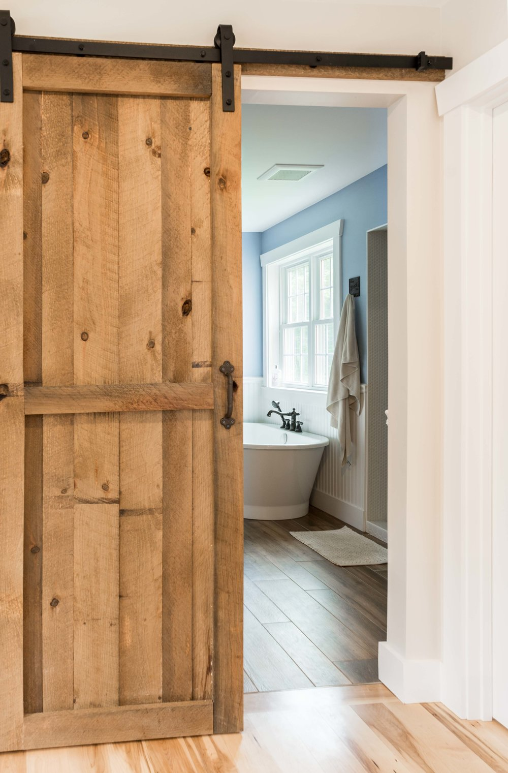 The sliding barn door was also made by the homeowner, and stained in Early American. The bathroom paint color is Notable Hue.