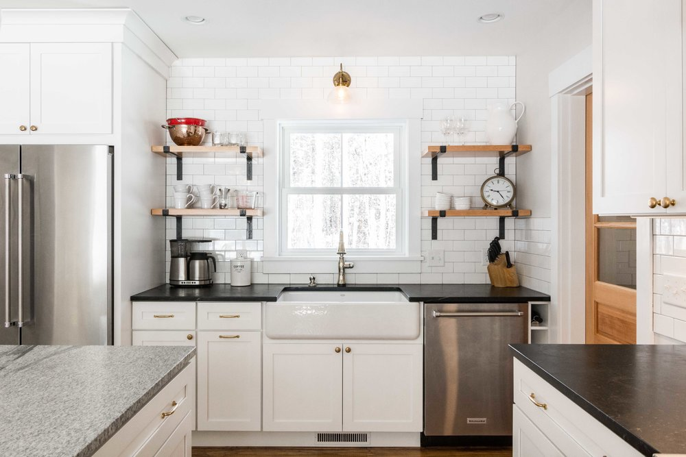 """Kohler Whitehaven 36""""farmhouse sink with a touch-on faucet. A  brass gooseneck sconce  sits above the sink."""