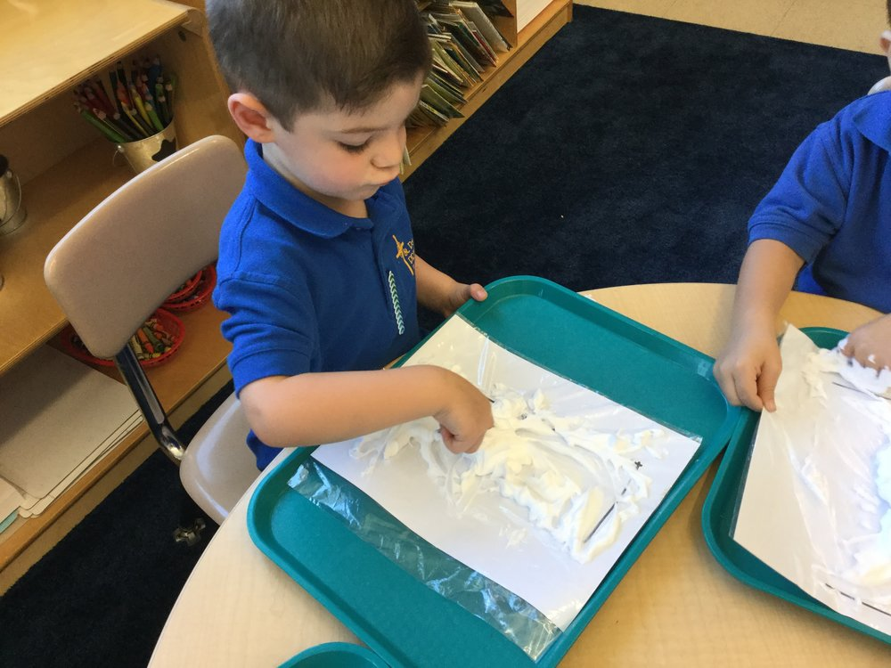 Tracing our letters with shaving cream.