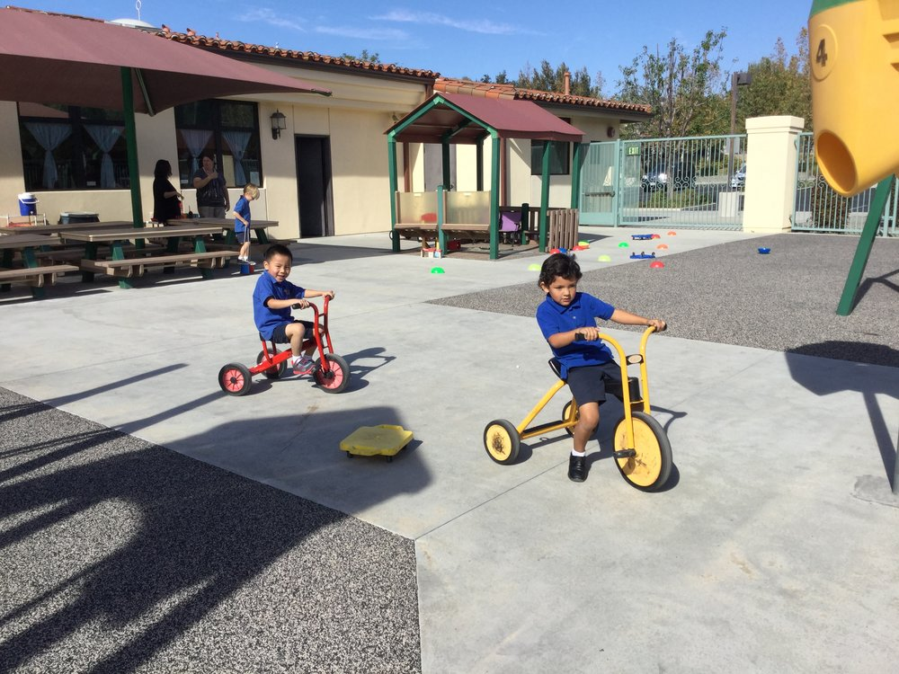 The children using the sit down scooters.