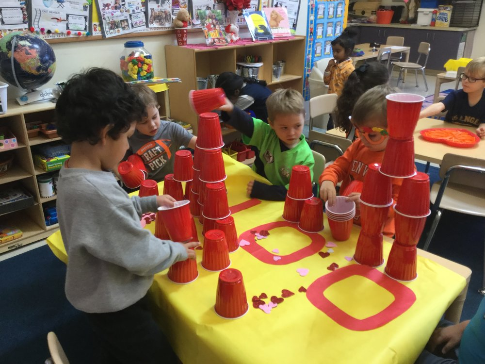 The children stacked up the 100 red cups in different patterns. They had a great time arranging the piles of cups.
