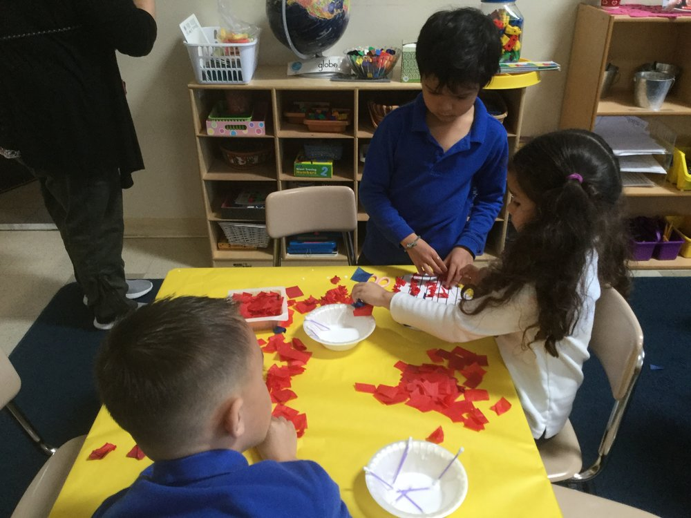 As a follow up art project the children made heart red, white and blue flags.  Their Kindergarten study buddies helped them with the project.  This activity is helping them with their fine motor skills.