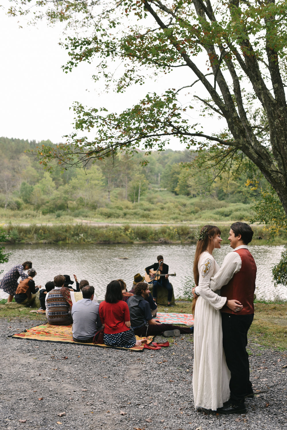 Mountain Wedding, Outdoors, Rustic, West Virginia, Maryland Wedding Photographer, DIY, Casual, bride and groom hugging and laughing with friend plays guitar
