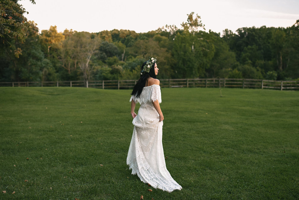 Maryland, Eastern Shore, Baltimore Wedding Photographer, Romantic, Boho, Backyard Wedding, Nature, Candid Photo of Bride Walking Through Field, Lace Daughters of Simone Wedding Dress, Flower Crown Michael Designs Florist