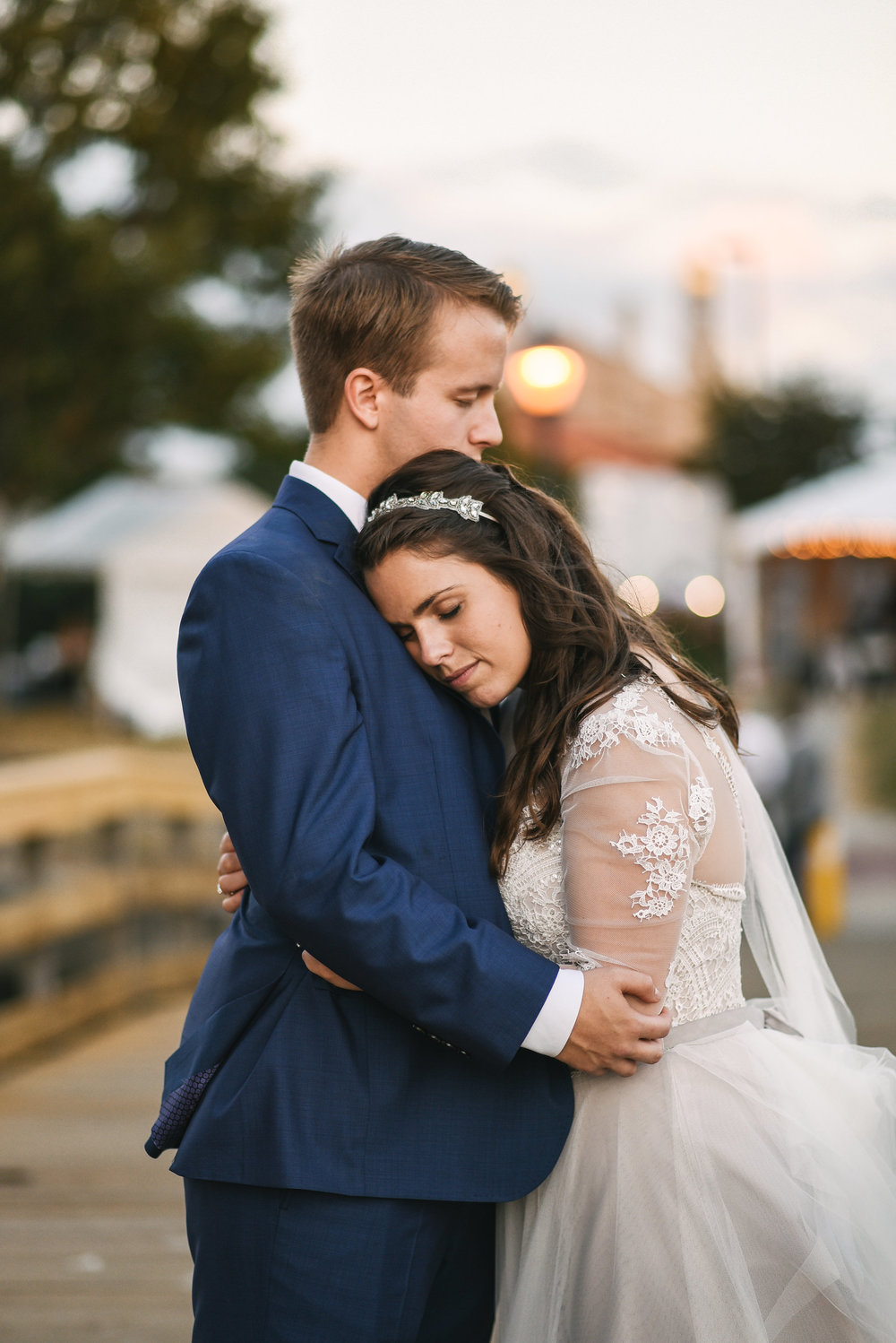 Baltimore, Canton, Modern, Outdoor Reception, Maryland Wedding Photographer, Romantic, Classic, Boston Street Pier Park, Bride and groom embracing, Lace wedding dress with sleeves, Blue suit