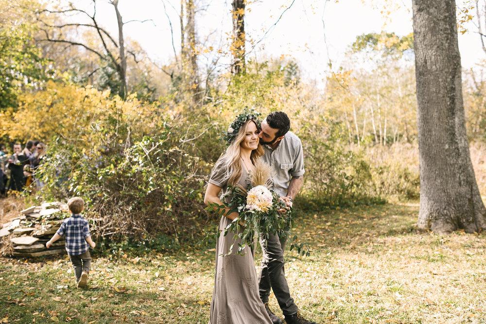Baltimore, Maryland Wedding Photographer, Backyard Wedding, DIY, Rustic, Casual, Fall Wedding, Woodland, Groom Kissing Bride on the Cheek While Their Son Runs Around, Butterbee Farm
