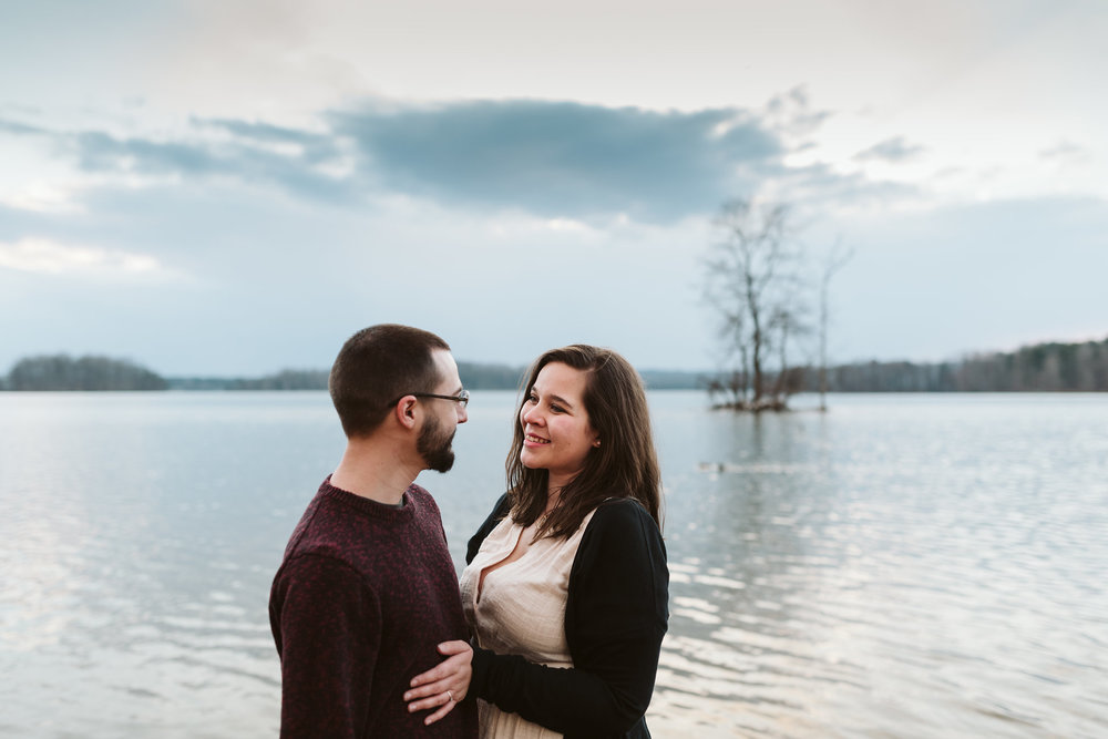 Baltimore County, Loch Raven Reservoir, Maryland Wedding Photographer, Winter, Engagement Photos, Nature, Romantic, Bride and Groom Smiling at Each Other in Front of Water, Outdoors, Rustic
