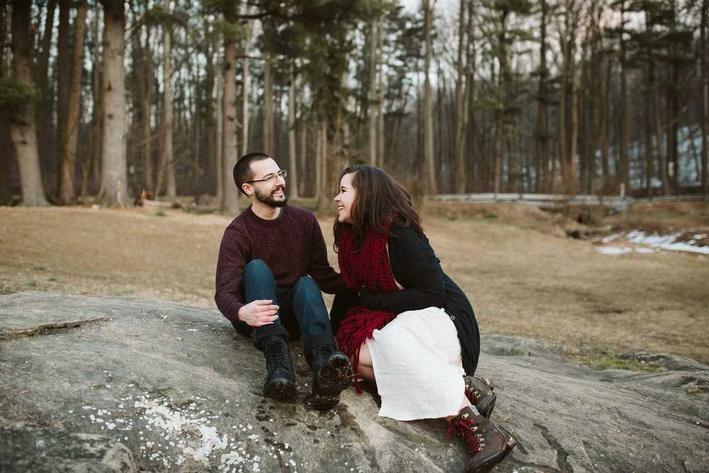 Baltimore County, Loch Raven Reservoir, Maryland Wedding Photographer, Winter, Engagement Photos, Nature, Romantic, Clean and Classic, Couple Laughing Together While Sitting on a Rock, Cold Morning, Spring