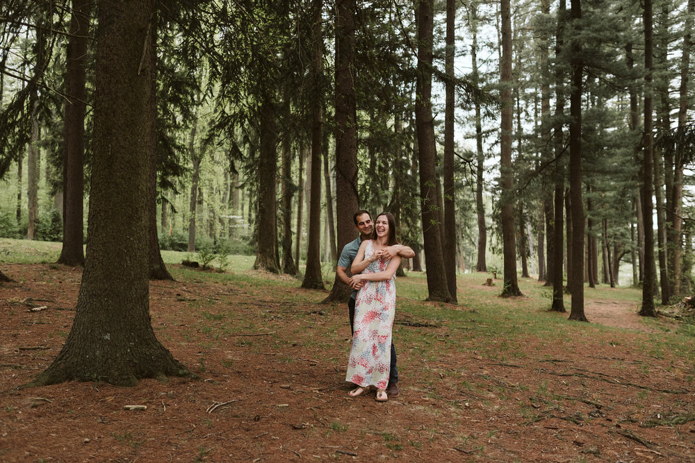 romantic couple dancing in forest on bed of pine needles
