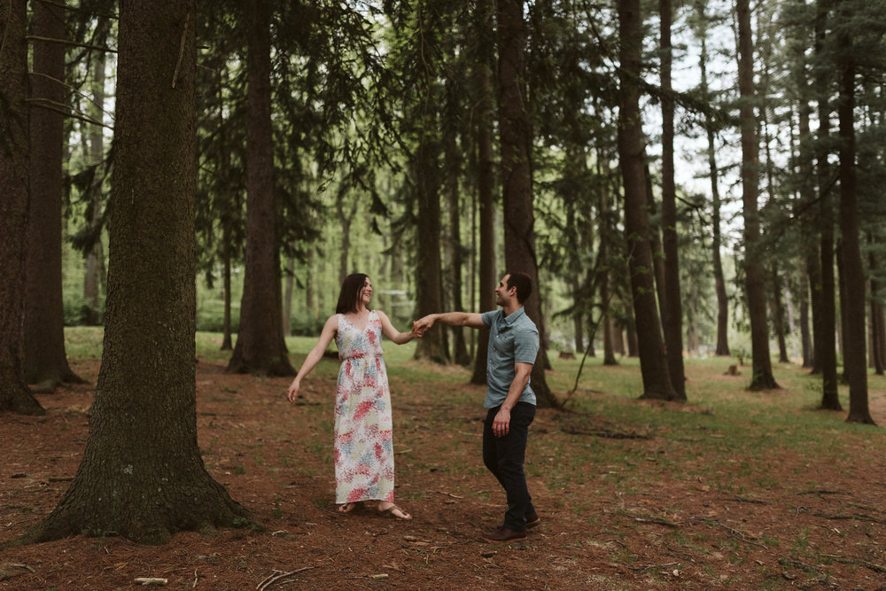 bride and groom dancing and twirling in a pine forest in maryland
