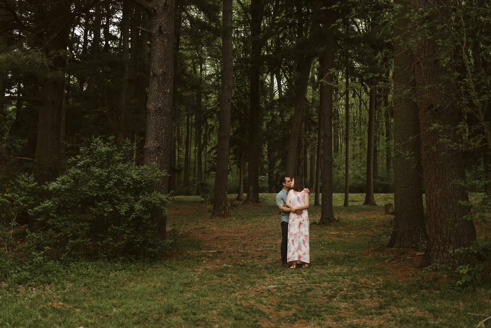 dark and moody photo of couple kissing in a pine forest wearing a long white dress and embracing
