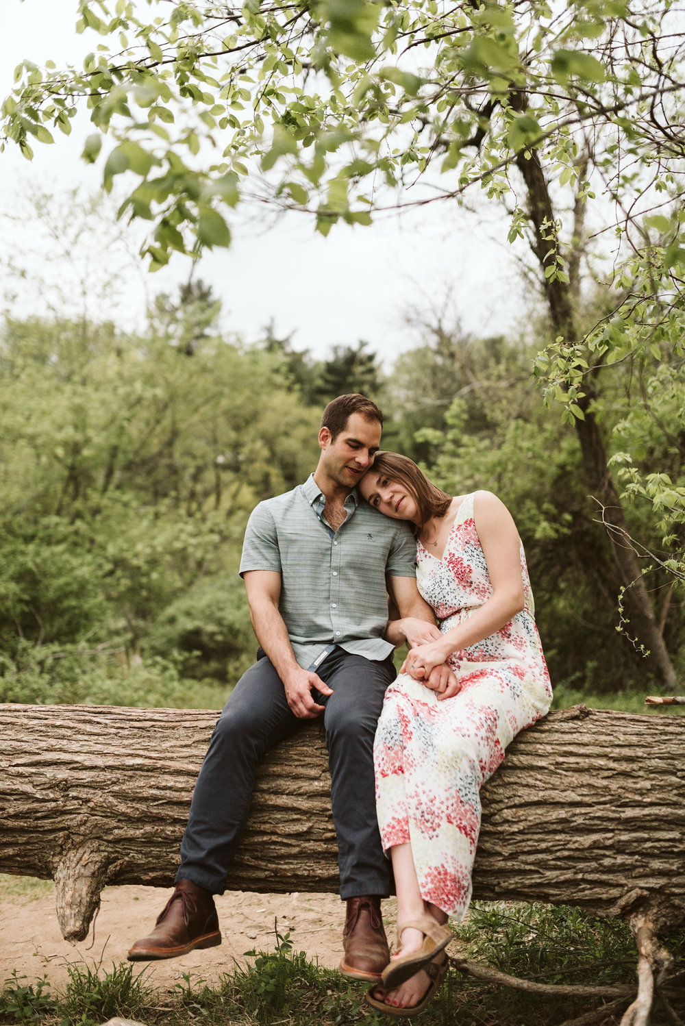 man and woman sitting on a log wearing long white dress and blue shirt for authentic engagement photos