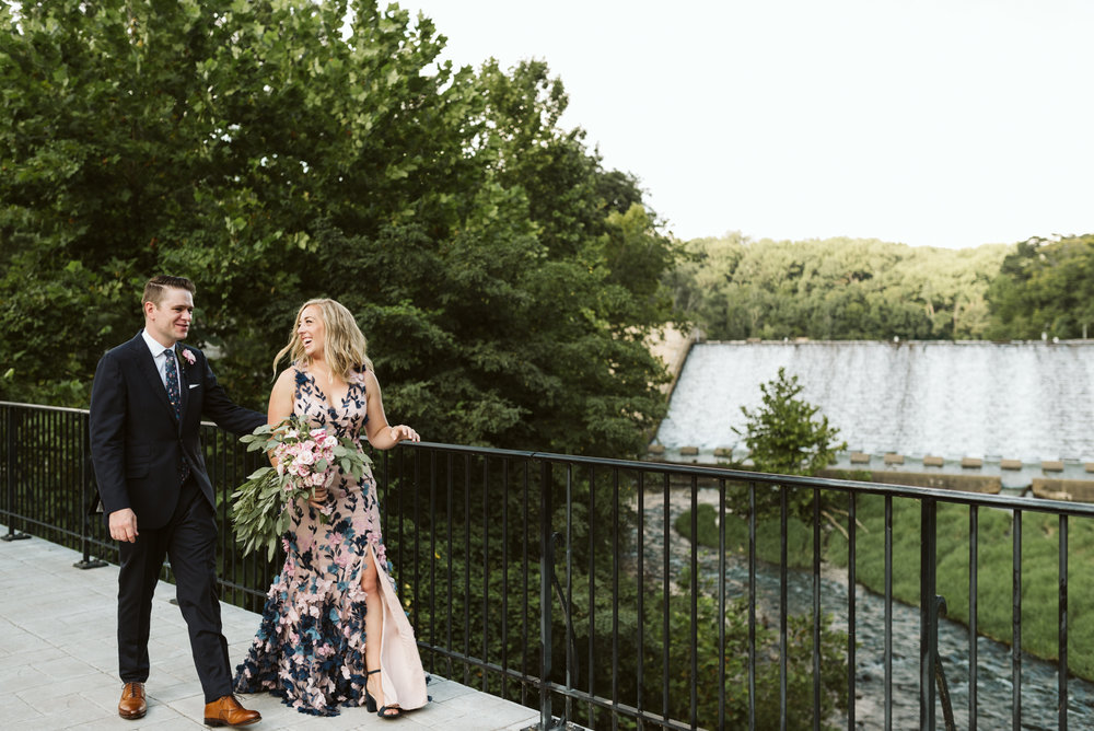 bride and groom walking over bridge at lake roland looking at water fall