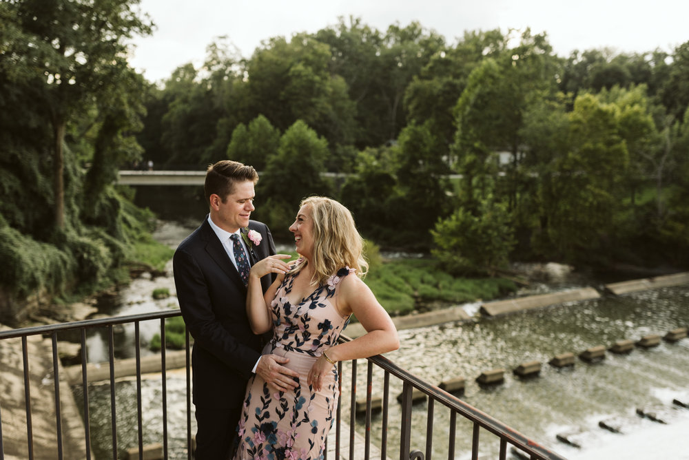 bride and groom leaning on bridge overlooking the water