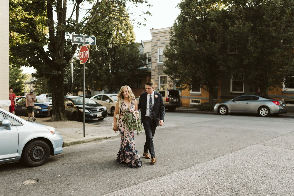 couple walking across street in hampden after wedding