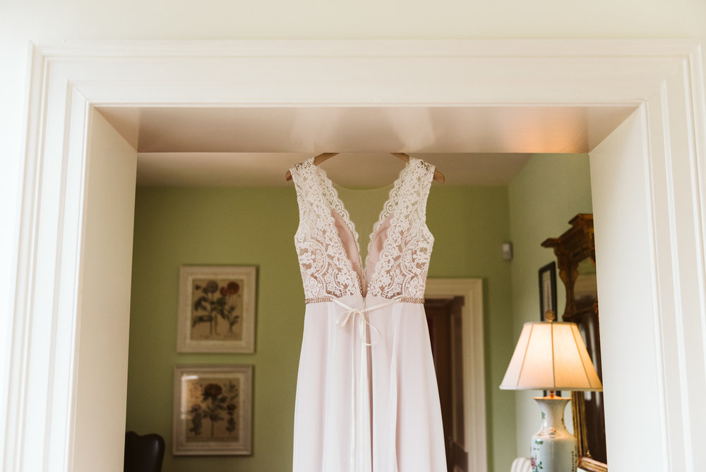 bhldn wedding dress hanging in doorway at columbia country club