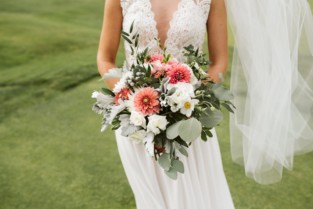 bride wearing bhdln wedding dress holding mint and coral flowers