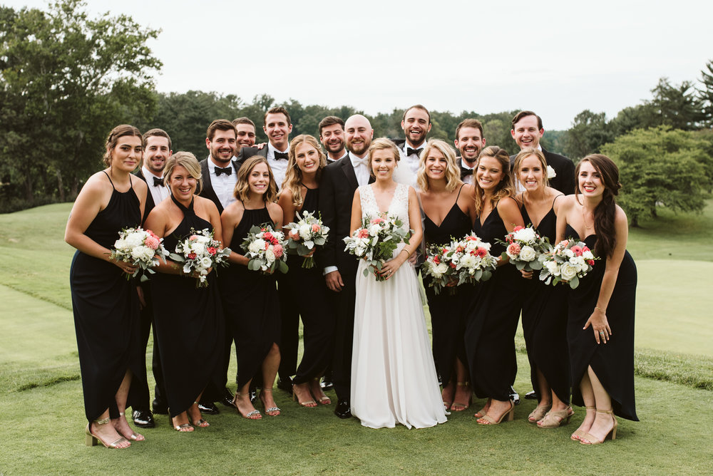large wedding party wearing all black and tuxes on golf course wedding