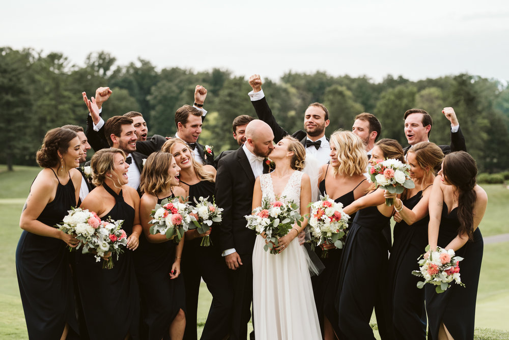 fun shot of the bride and groom kissing while wedding party cheers them on