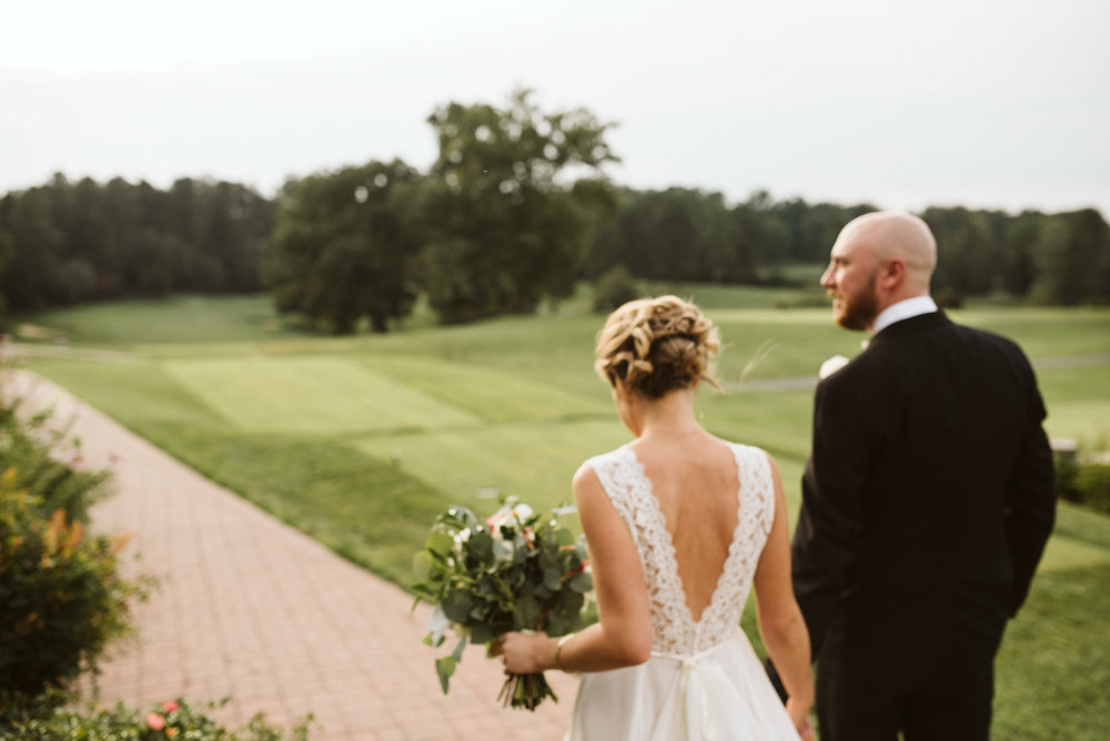 artistic photo of couple from behind wearing tux and bhldn wedding gown