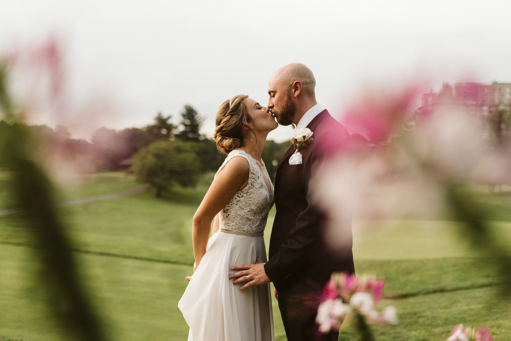 romantic photo through pink flowers in foreground on wedding day