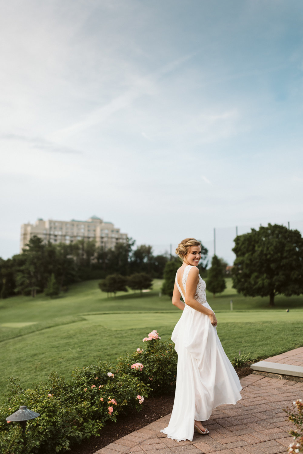 beautiful bride walking down path at sunset with green grass and flowers in bhldn dress