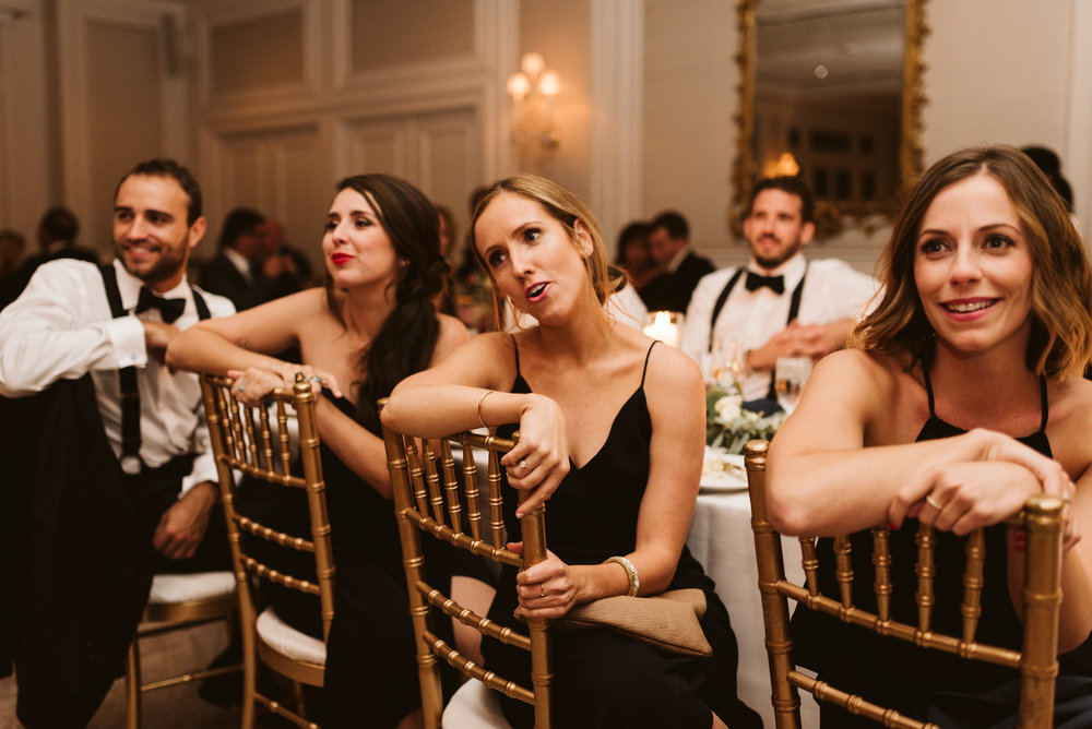 bridesmaids watching couple have first dance saying aww
