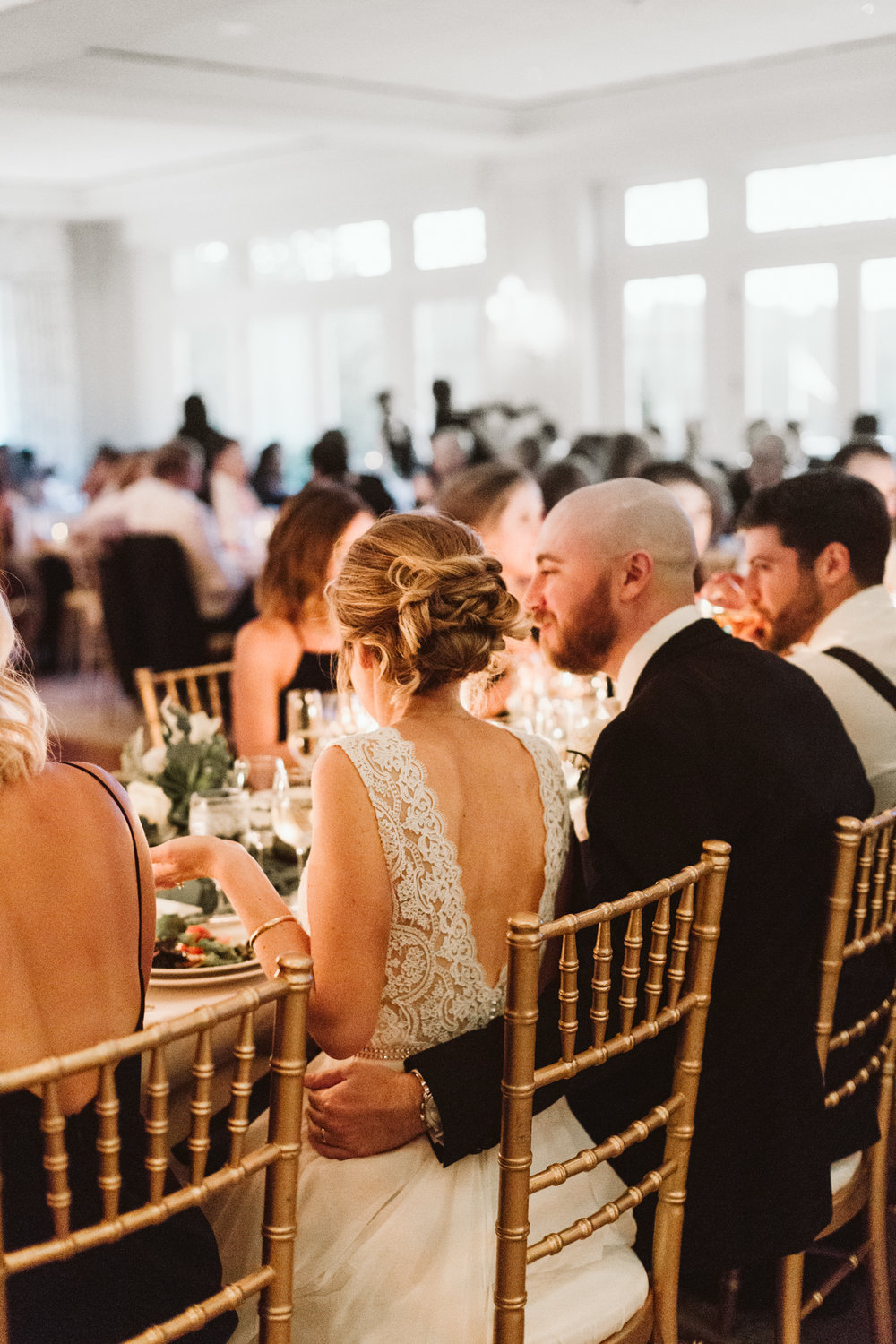 romantic candlelit photo of bride and groom sitting in gold chairs at dinner table