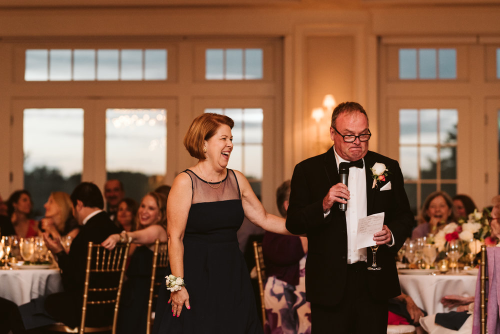 mom and dad giving toasts at columbia country club and guests laughing