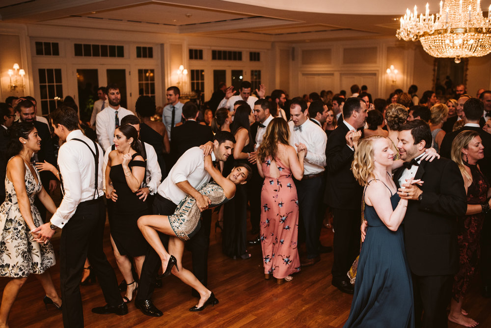 dramatic wide photo of dance floor at black tie wedding with the bachelor boys band
