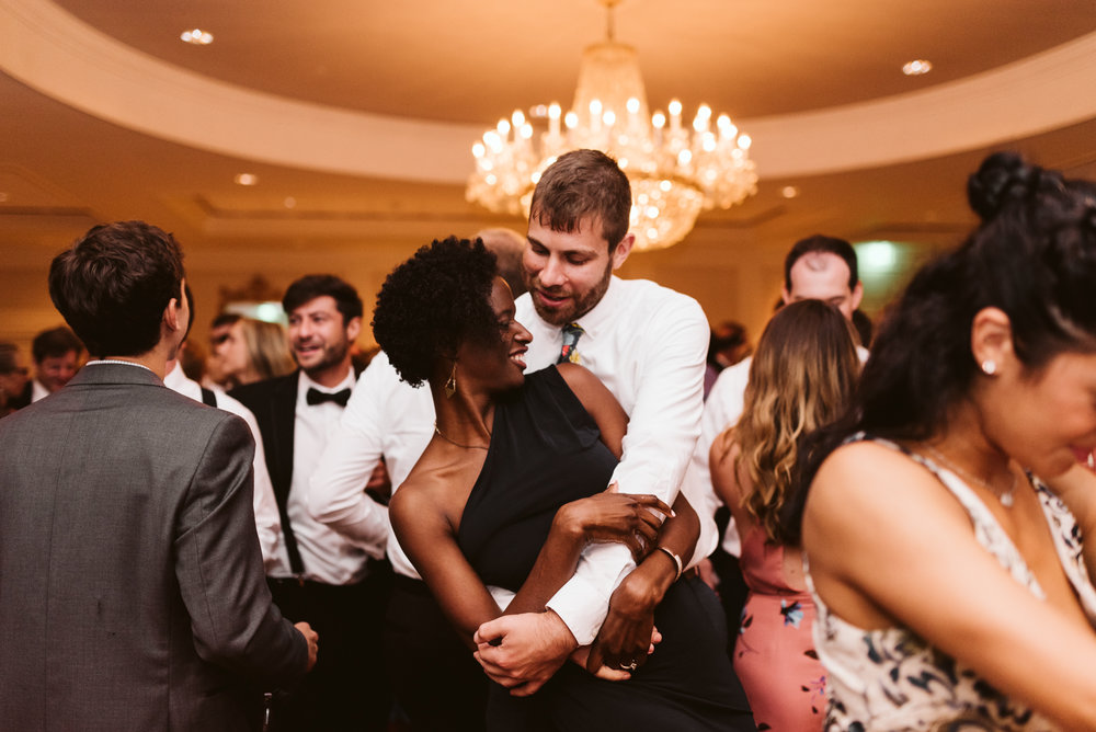 cute couple of wedding guests dancing and embracing on dance floor surrounded by people