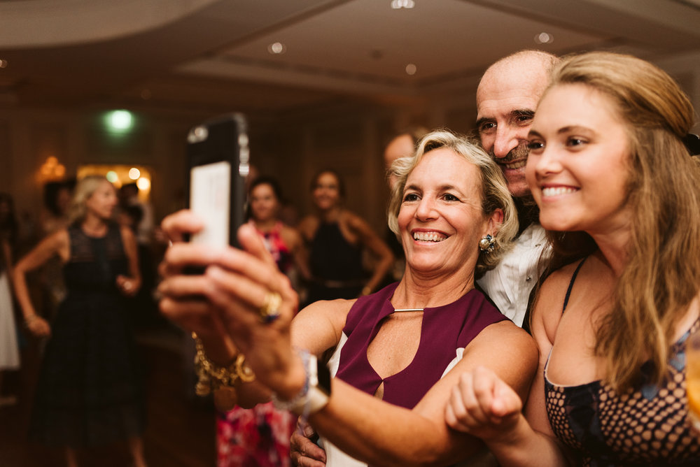 family taking a selfie at a wedding