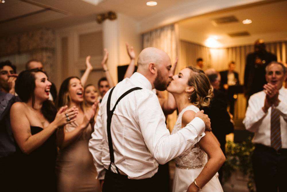 bride and groom kissing on dance floor at the end of the wedding night