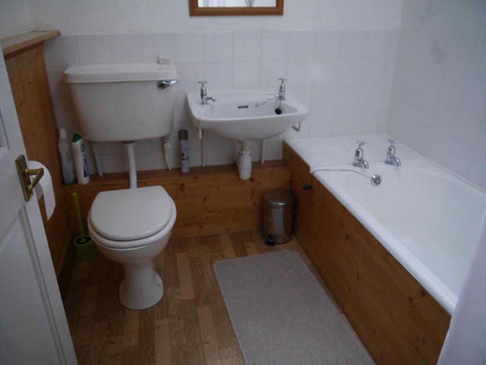The bathroom has an electric shower over the bath