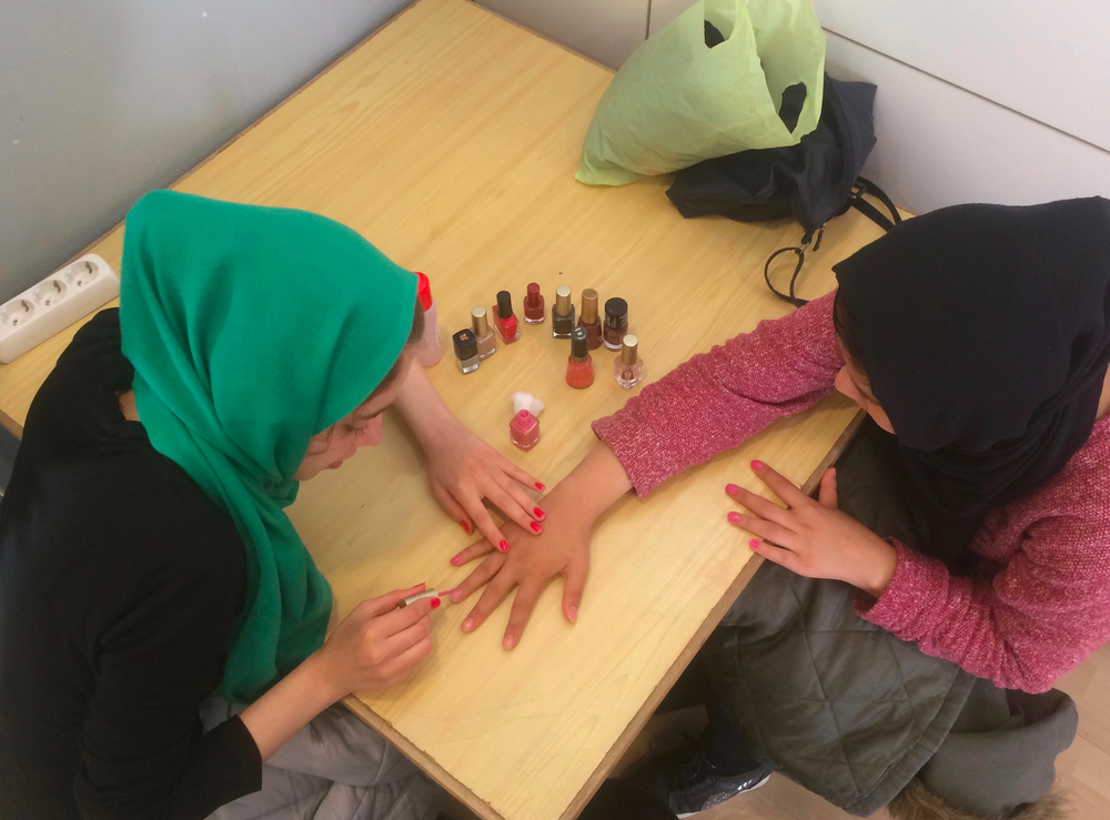 Two young women paint each others' nails during the women's only Saturday session at Alpha Centre in Samos. By Melissa Pawson. Samos, Greece: 2018. JPG file.