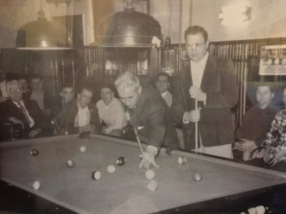 "World champion Willie Mosconi takes a shot in my grandfather's pool hall as Pete Leggieri of Hudson looking on. More than 100 people watched in 1954 as Mosconi beat Leggieri in a ""hard, well-played game"" according to the local newspaper."