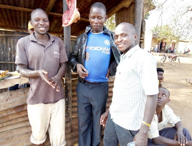 Matsiko Brian in white shirt (Auxiliary Paralegal) and Okello in blue Chelsea shirt at his workplace