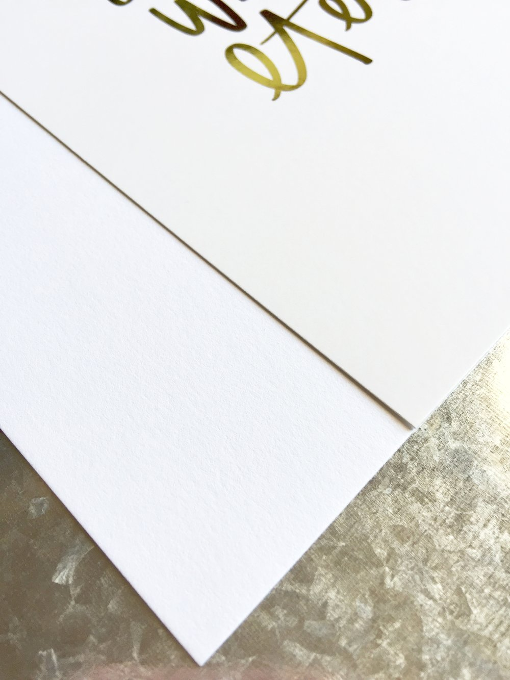 On the left, the paper our Classic Prints are printed on. On the right, our Gold Foil Prints.