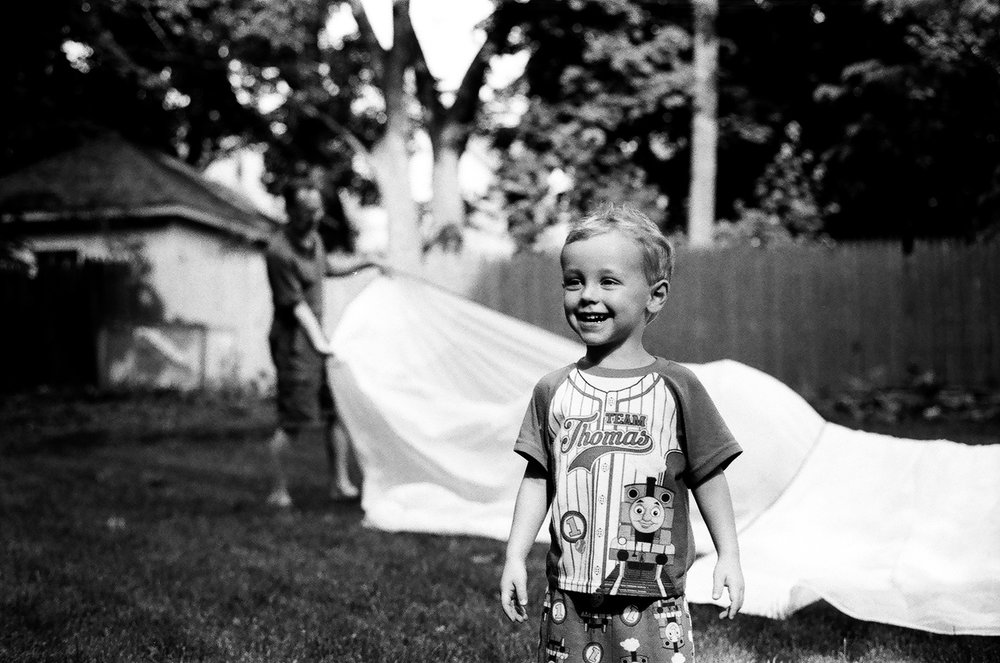 """My nephew Avi """"helping"""" fold a sail for the first time with his Grandfather"""