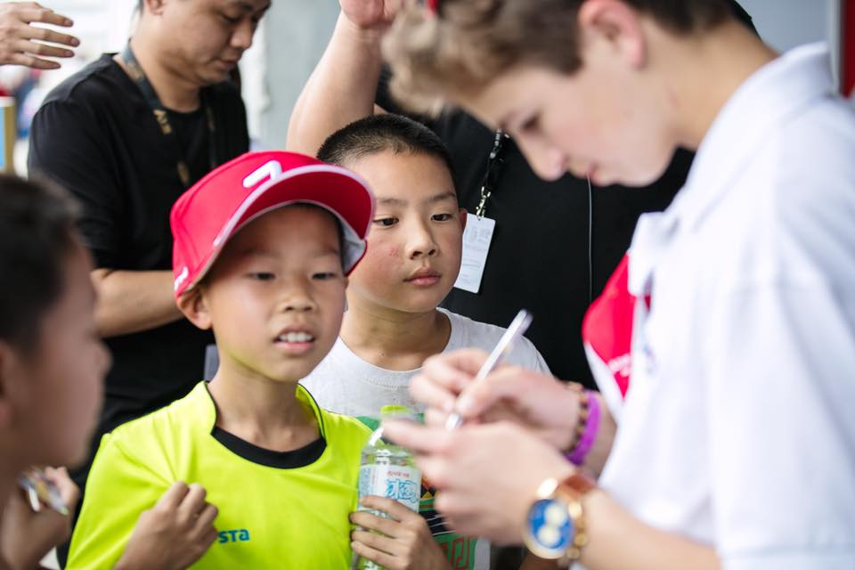 Bruno Carneiro signs autographs to his young fans during the 2016 FIA F4 race in Chengdu, China (May 2016)